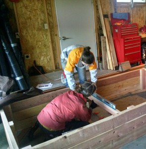 Elise D'Alessandro and Amanda Harper construct a raised bed.